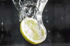 A slice of lemon drops into the water. With a spray. Close up Stock Photography