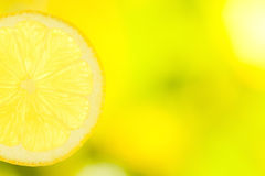 Slice of lemon on green and yellow background Royalty Free Stock Images