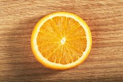 A slice of lemon, isolated on a wooden background Royalty Free Stock Images