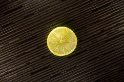 Slice of lemon or lime on black background with stripes. Picture presents slice of lemon or lime on white background Royalty Free Stock Photos