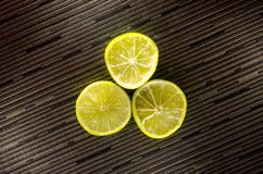 Slice of lemon or lime on black background with stripes. Picture presents slice of lemon or lime on white background Royalty Free Stock Images