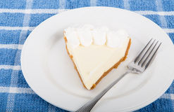 Slice of Lemon Pie on Plate. Slice of fresh lemon meringue pie on a white plate with fork on blue plaid placemat Stock Photography