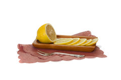 Slice lemon on the plate with silverware on a napkin  on. Slice lemon on the plate with silverware on a  on white background Stock Photos