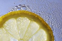 Slice of lemon in sparkling water. Close up of a lemon slice in sparkling water, something refreshing to drink in a hot summer royalty free stock photography