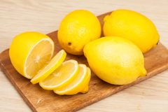 Slice lemon on wood chopping. Board with background, close up Stock Photos