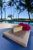 Slice of lilikoi cheesecake on a beautiful Hawaiian day. Slice of lilikoi cheesecake by the poolside stock photo
