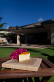 Slice of lilikoi cheesecake on a beautiful Hawaiian day. Slice of lilikoi cheesecake by the poolside stock images