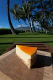 Slice of lilikoi cheesecake on a beautiful Hawaiian day. Slice of lilikoi cheesecake by the poolside royalty free stock images