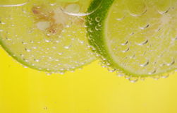 Slice of Lime. Slices of lime in a refreshing drink. Bright yellow background Stock Photos