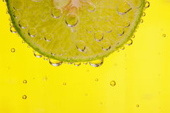 Slice of Lime. A slice of lime in a refreshing drink. Bright yellow background Stock Photo