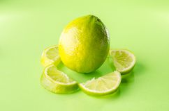 Slice of lime around one whole on green background, horizontal shot. Picture presents slice of lime around one whole on green background, horizontal shot Stock Images