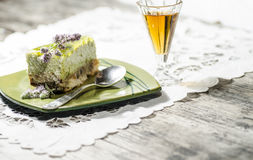 Slice of lime cheesecake decorated with mint flowers and glass of cognac, blurred background Stock Photography