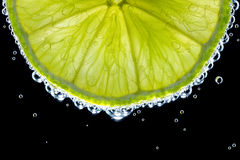 Slice of lime in the gas water on the black.  Royalty Free Stock Images