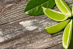 Slice  lime 4. Slice of lime with leaves on a piece of wood Royalty Free Stock Image