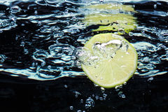 Slice of lime (lemon)  falling in water Stock Photos