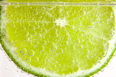 Slice of lime  in the water with bubbles Stock Images