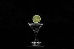Slice of lime water dropped into a glass Royalty Free Stock Images