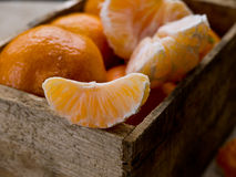 Slice of Mandarin Orange or Clementines. A wooden box full of fresh citrus mandarin oranges or clementines. A single slice in focus stock images