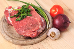 Slice of meat on the cutting board with spices, onion, garlic an stock photo