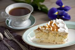 Slice of meringue cake and a cup of tea and iris stock photos