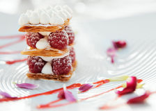 Slice of mille-feuille cake with raspberries. And sweet sauce on porcelain plate Stock Photos