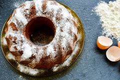 Bundt lemon cake. Slice of moist lemon bundt cake on black slate Stock Images