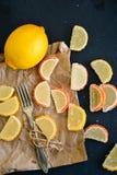 Lemon slices. Slice of moist lemon bundt cake  and   lemon and orange slices  on black slate Stock Photography