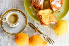 Bundt lemon cake. Slice of moist lemon bundt cake with real lemons and vintage cup of coffee on white wooden background royalty free stock photos