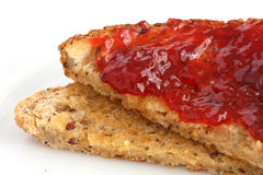 Slice of multi-seed wholegrain bread toasted and buttered with jam. Royalty Free Stock Photo