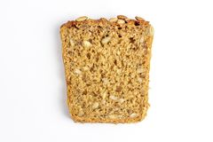 Slice of multigrain bread with sunflower and pumpkin seeds and flax seed on a white background royalty free stock images