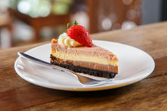 Slice of muti layer cheese cake with strawberry on the wooden ta Stock Photos
