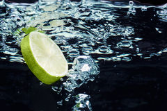 Slice Of Lime (lemon) Falling In Water Royalty Free Stock Images