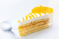 Slice of Orange Cheesecake. A slice of orange cheesecake with the spoon that prompt to joy it Stock Photo