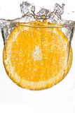 Slice orange falling into the water Royalty Free Stock Photography