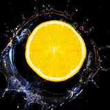 Slice of orange falls into the water. Royalty Free Stock Photo