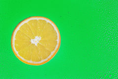 Slice of orange on green Stock Photo
