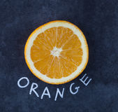 Slice of orange with handwritten text label. Slice of orange with text label on dark grungy surface. Top view Stock Photography