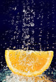 Slice of orange with stopped motion water drops Royalty Free Stock Photos
