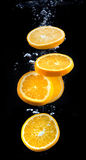 Slice of orange in the water with bubbles Royalty Free Stock Photos