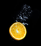 Slice of orange in the water with bubbles Royalty Free Stock Photography