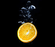 Slice of orange in the water with bubbles Stock Photo