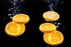 Slice of orange in the water with bubbles Royalty Free Stock Photo
