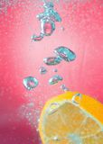 Slice of orange in the water with bubbles, on red background Royalty Free Stock Photo