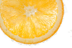 Slice orange in water on white background Royalty Free Stock Images