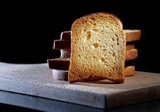 Slice ot toast. Close up of toasted white bread in slices on cutting board over black background Stock Images