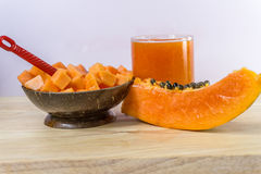 Slice of papaya isolated on the wooden table. Papaya, smoothie, isolated, fruit, Slice of papaya with juice isolated on the wooden table stock photos
