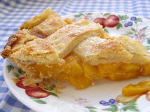 Slice of peach pie. On blue checkered napkin Stock Photos