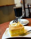 Slice of pear cream cake and glass cup of black coffee Royalty Free Stock Images