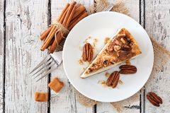 Slice of pecan caramel cheesecake, top view over white wood. Slice of pecan caramel cheesecake, top view on a rustic white wood background Royalty Free Stock Photos