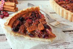 Slice of pecan cranberry pie on paper against white wood Stock Photography